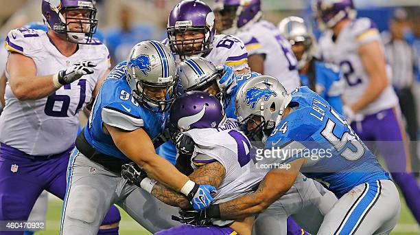 Matt Asiata of the Minnesota Vikings is stopped by Ndamukong Suh and DeAndre Levy of the Detroit Lions during the third quarter of the game at Ford...