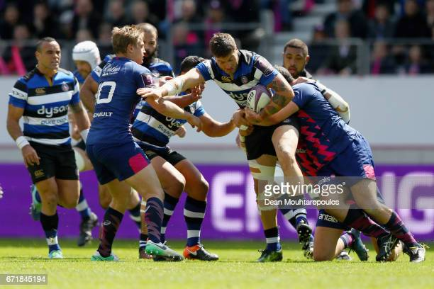 Matt Banahan of Bath Rugby is stopped with a tackle by Jules Plisson and Laurent Panis of Stade Francais during the European Rugby Challenge Cup...