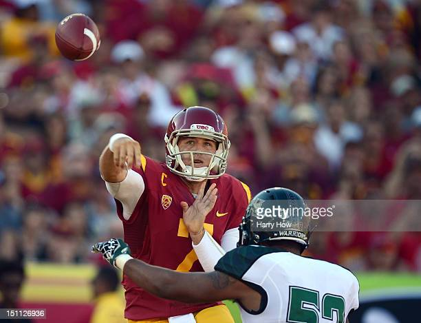 Matt Barkley of the USC Trojans makes a throw over Kendrick Van Ackeren of the Hawaii Warriors during the first quarter at Los Angeles Coliseum on...