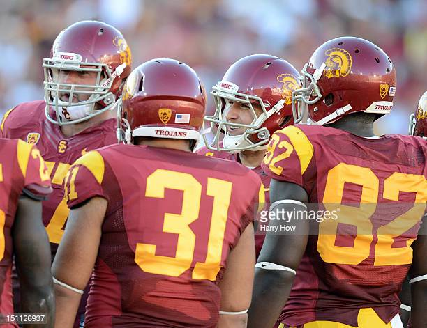 Matt Barkley of the USC Trojans smiles before a huddle with Kevin Graf Soma Vainuku and Randall Telfer during the game against the Hawaii Warriors at...
