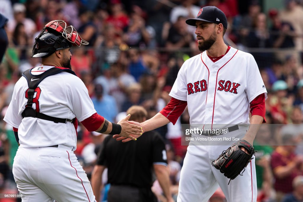 Matt Barnes #59 and Sandy Leon #3 of the Boston Red Sox celebrate a victory against the Seattle Mariners on June 24, 2018 at Fenway Park in Boston, Massachusetts.