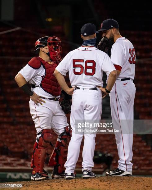 Matt Barnes meets with Christian Vazquez and pitching coach Dave Bush of the Boston Red Sox during the eighth inning of a game against the Toronto...