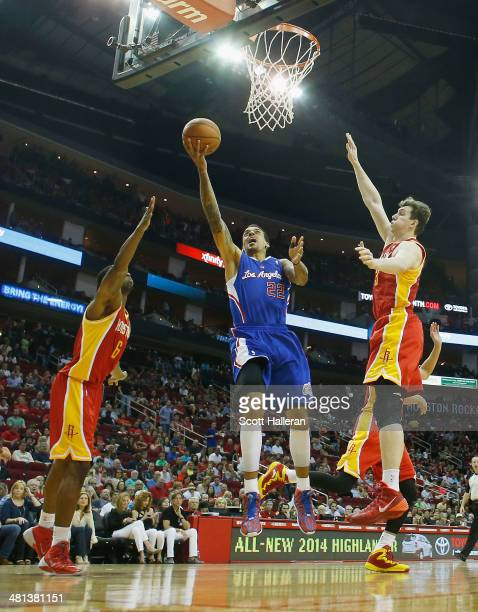 Matt Barnes of the Los Angeles Clippers shoots over Terrence Jones and Omer Asik of the Houston Rockets during the game at the Toyota Center on March...