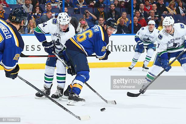 Matt Bartkowski and Linden Vey of the Vancouver Canucks look to get the puck past Paul Stastny of the St Louis Blues at the Scottrade Center on March...