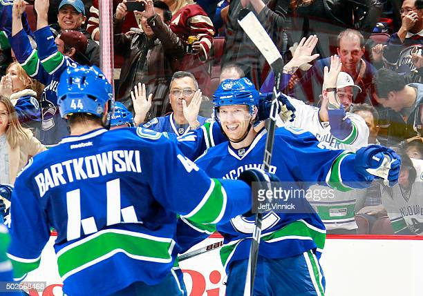 Matt Bartkowski congratulates Jannik Hansen of the Vancouver Canucks who scored the overtime winning goal against the Edmonton Oilers during their...