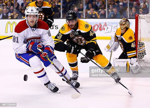 Matt Bartkowski of the Boston Bruins and Lars Eller of the Montreal Canadiens chase down a puck into the corner in the first overtime period in Game...