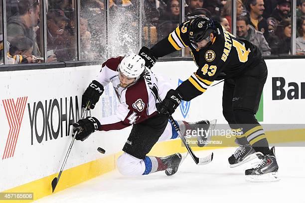 Matt Bartkowski of the Boston Bruins checks against Dennis Everberg of the Colorado Avalanche at the TD Garden on October 13, 2014 in Boston,...