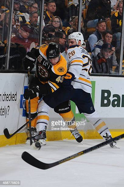 Matt Bartkowski of the Boston Bruins fights foe the puck against Zemgus Girgensons of the Buffalo Sabres at the TD Garden on December 21, 2013 in...