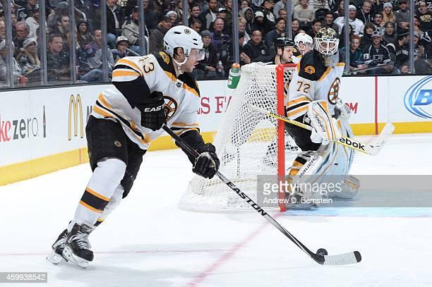 Matt Bartkowski of the Boston Bruins handles the puck while Niklas Svedberg of the Boston Bruins looks on at STAPLES Center on December 02 2014 in...