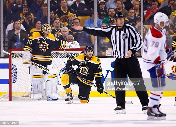 Matt Bartkowski of the Boston Bruins kneels in front of teammate Tuukka Rask after being called for a penalty in the second overtime period against...