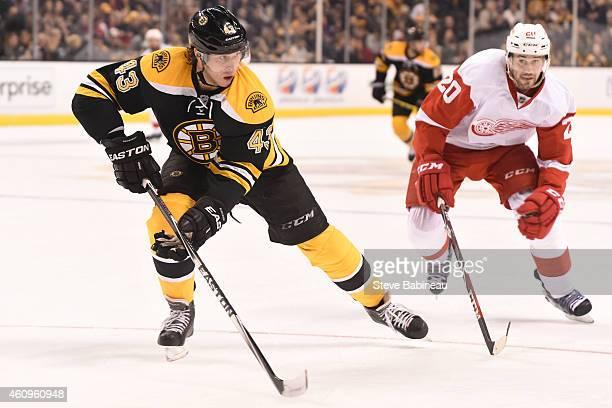 Matt Bartkowski of the Boston Bruins skates against Drew Miller of the Detroit Red Wings at the TD Garden on December 29, 2014 in Boston,...