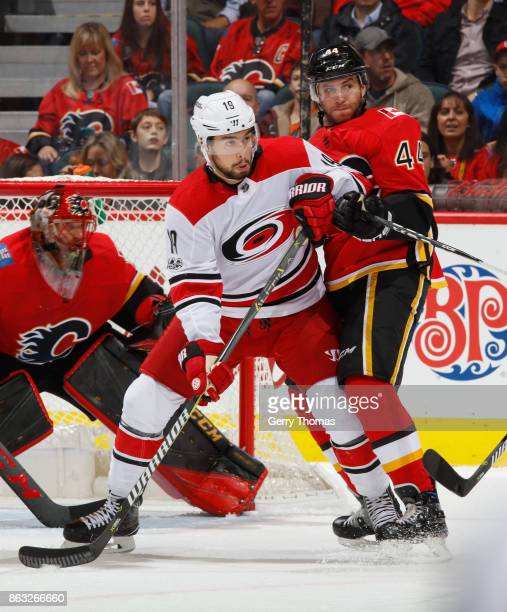 Matt Bartkowski of the Calgary Flames battles against Josh Jooris of the Carolina Hurricanes at Scotiabank Saddledome on October 19 2017 in Calgary...