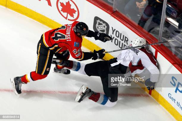 Matt Bartkowski of the Calgary Flames checks Joe Colborne of the Colorado Avalanche during an NHL game on March 27 2017 at the Scotiabank Saddledome...