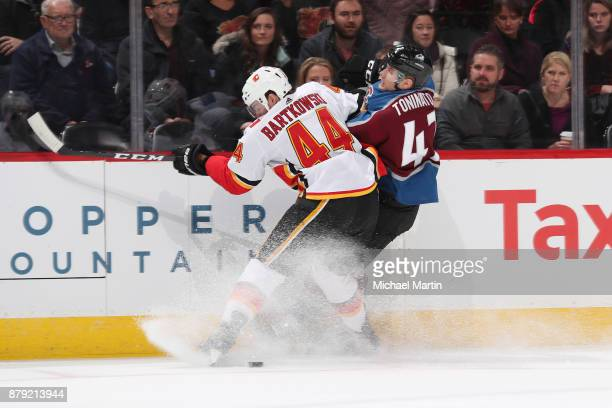 Matt Bartkowski of the Calgary Flames fights for position against Dominic Toninato of the Colorado Avalanche at the Pepsi Center on November 25 2017...