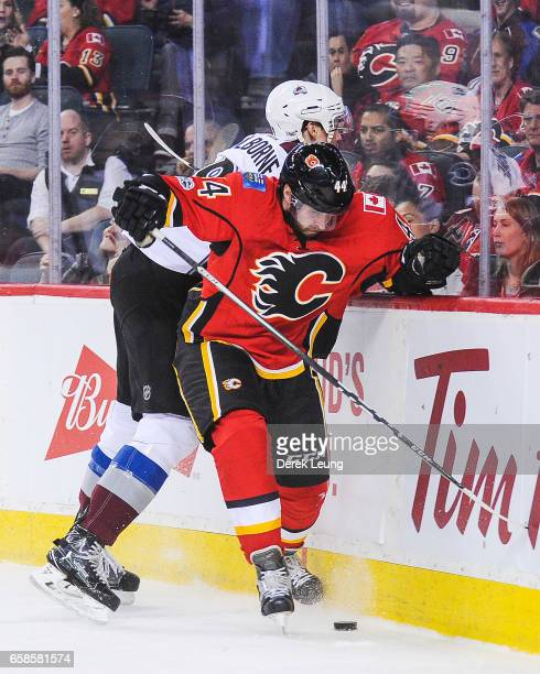 Matt Bartkowski of the Calgary Flames fights for the puck against Joe Colborne of the Colorado Avalanche during an NHL game at Scotiabank Saddledome...