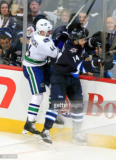 Matt Bartkowski of the Vancouver Canucks and Anthony Peluso of the Winnipeg Jets collide along the boards during second period action at the MTS...