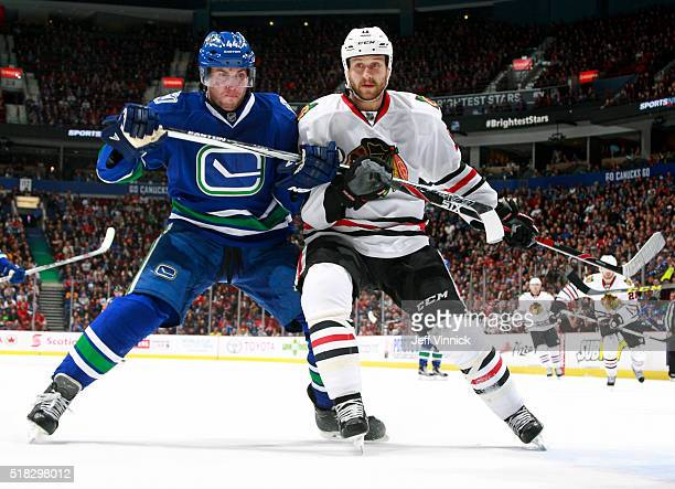 Matt Bartkowski of the Vancouver Canucks checks Andrew Desjardins of the Chicago Blackhawks during their NHL game at Rogers Arena March 27 2016 in...