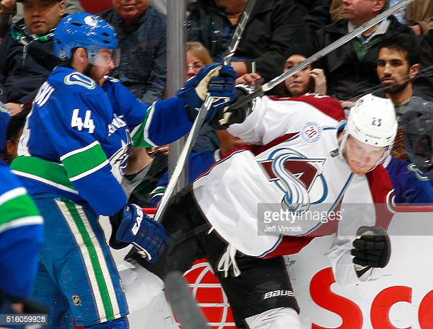 Matt Bartkowski of the Vancouver Canucks checks Mikhail Grigorenko of the Colorado Avalanche during their NHL game at Rogers Arena March 16, 2016 in...