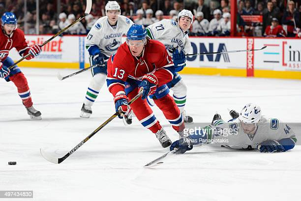 Matt Bartkowski of the Vancouver Canucks defends the puck from the ice against Alexander Semin of the Montreal Canadiens during the NHL game at the...