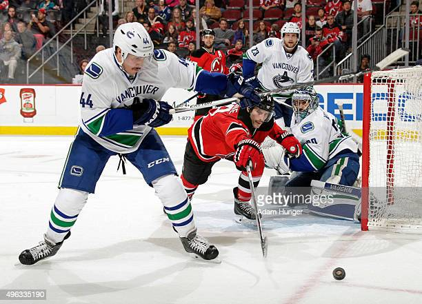 Matt Bartkowski of the Vancouver Canucks looks to clear the puck in front of Adam Henrique of the New Jersey Devils during overtime at the Prudential...