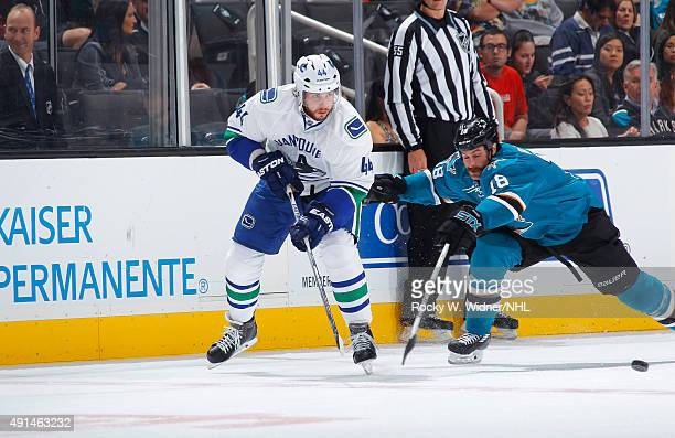 Matt Bartkowski of the Vancouver Canucks passes the puck against Mike Brown of the San Jose Sharks at SAP Center on September 29 2015 in San Jose...