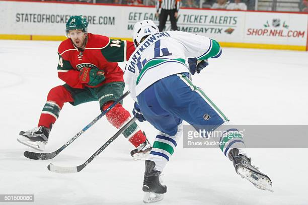Matt Bartkowski of the Vancouver Canucks shoots the puck with Justin Fontaine of the Minnesota Wild defending during the game on December 15 2015 at...