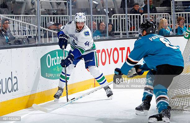 Matt Bartkowski of the Vancouver Canucks skates with the puck against Joe Pavelski of the San Jose Sharks at SAP Center on September 29 2015 in San...