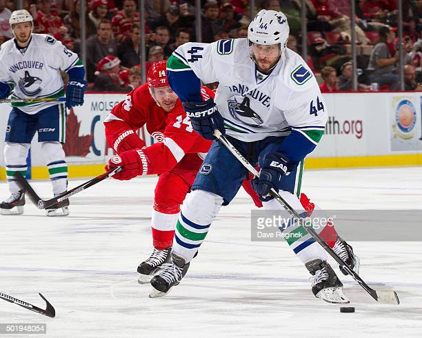 Matt Bartkowski of the Vancouver Canucks skates with the puck in front of Gustav Nyquist of the Detroit Red Wings during an NHL game at Joe Louis...