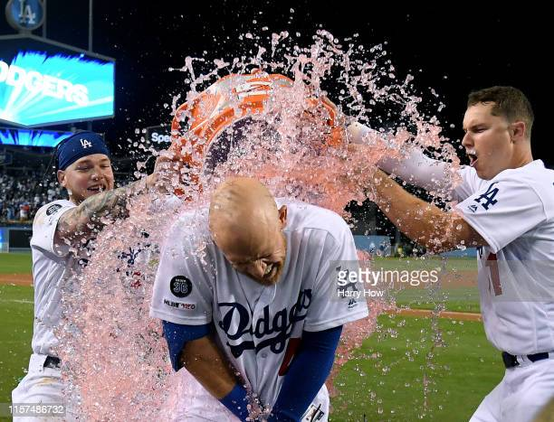 Matt Beaty of the Los Angeles Dodgers is showered with Gatorade by Joc Pederson and Alex Verdugo after his two run homerun for a 42 win over the...