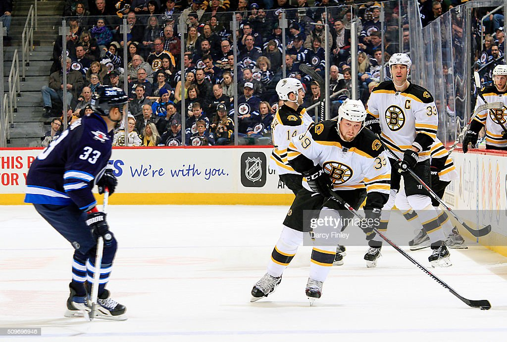 Matt Beleskey #39 of the Boston Bruins plays the puck down the ice as Dustin Byfuglien #33 of the Winnipeg Jets looks on during third period action at the MTS Centre on February 11, 2016 in Winnipeg, Manitoba, Canada.