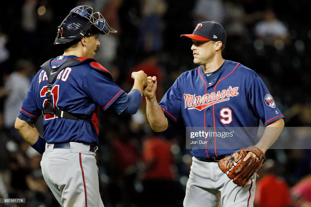 Matt Belisle #9 of the Minnesota Twins (R) and Jason Castro #21 fist bump after their win over the Chicago White Sox at Guaranteed Rate Field on August 22, 2017 in Chicago, Illinois.The Minnesota Twins won 4-1.