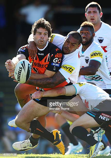 Matt Bell of the Tigers looks to off load to a team mate during the round two NRL match between the Wests Tigers and the Penrith Panthers at...