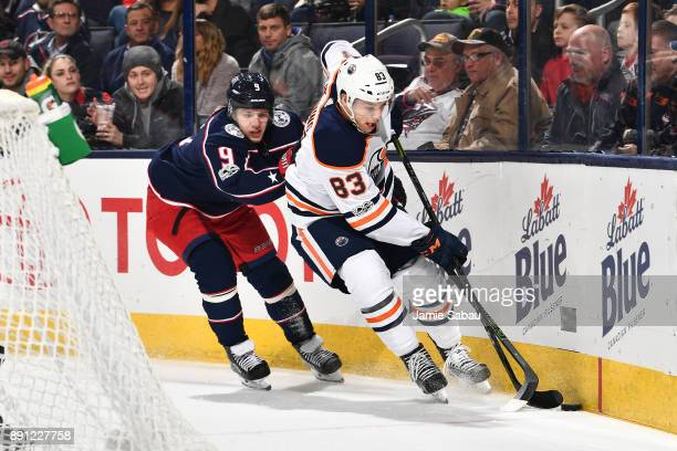 Matt Benning of the Edmonton Oilers attempts to keep the puck from Artemi Panarin of the Columbus Blue Jackets during the first period of a game on...