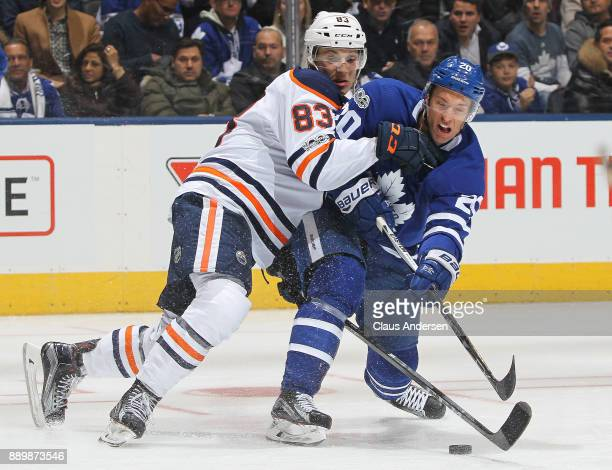 Matt Benning of the Edmonton Oilers battles against Dominic Moore of the Toronto Maple Leafs during an NHL game at the Air Canada Centre on December...