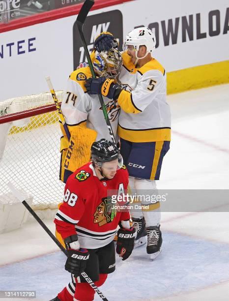 Matt Benning of the Nashville Predators hugs Juuse Saros after a win as Patrick Kane of the Chicago Blackhawks skates off the ice at the United...