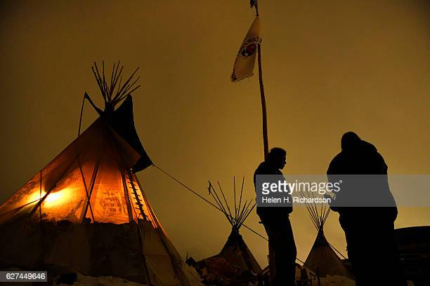 Matt Black Eagle Man, middle, a member of the Long Plain First Nation, chats with friends outside of his teepee at Oceti Sakowin Camp on the edge of...
