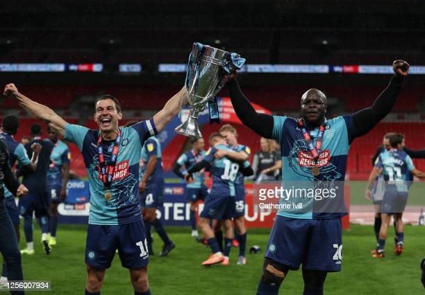 Matt Bloomfield and Adedbayo Akinfenwa of Wycombe Wanderers celebrate with the trophy after the Sky Bet League One Play Off Final between Oxford...