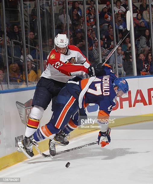 Matt Bradley of the Florida Panthers hits Andrew MacDonald of the New York Islanders at the Nassau Veterans Memorial Coliseum on October 8, 2011 in...