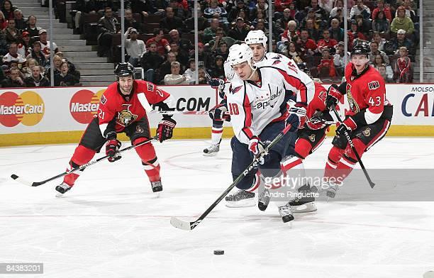 Matt Bradley the Washington Capitals stickhandles the puck against Jason Smith and Peter Regin of the Ottawa Senators at Scotiabank Place on January...