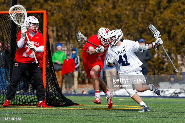 Matt Brandau of the Yale Bulldogs dodges to the goal against the defense of Dom Doria of the Cornell Big Red during the second half at Reese Stadium...