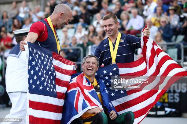 Matt Brumby of Australia shares a moment with medalists Joshua Smith and Patrick Ryan Novack of the United States after winning the Men's 100m IT4...