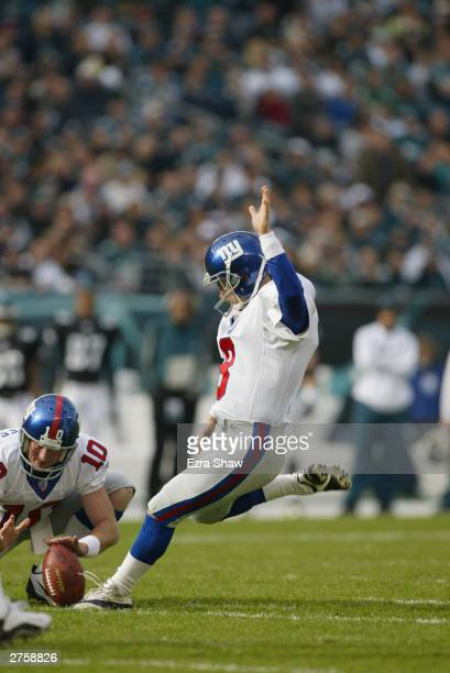 Matt Bryant of the New York Giants kicks a 30 yard field goal against the Philadelphia Eagles out of the hold of teammate Jeff Feagles to give the...