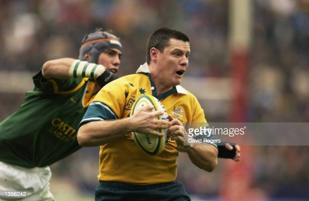 Matt Burke of Australia escapes the tackle of Marius Joubert of South Africa during the Tri Nations Rugby Union International match between South...