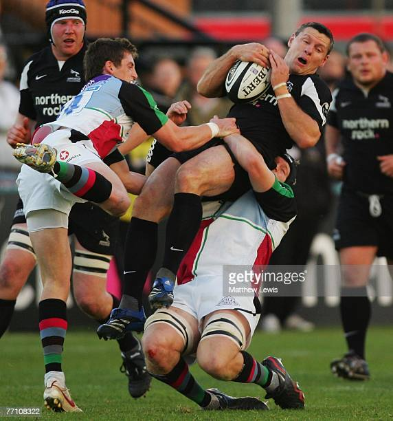 Matt Burke of Newcastle is tackled by Jim Evans of Harlequins during the Guinness Premiership match between Newcastle Falcons and Harlequins at...