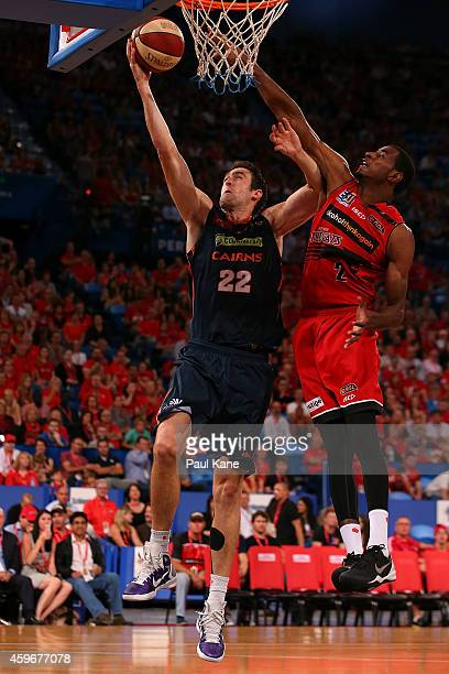Matt Burston of the Taipans lays up against DeAndre Daniels of the Wildcats during the NBL round eight game between the Perth Wildcats and the Cairns...