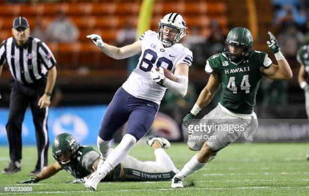 Matt Bushman of the BYU Cougars is chased by Russell Williams Jr of the Hawaii Rainbow Warriors after breaking free from Solomon Matautia during the...