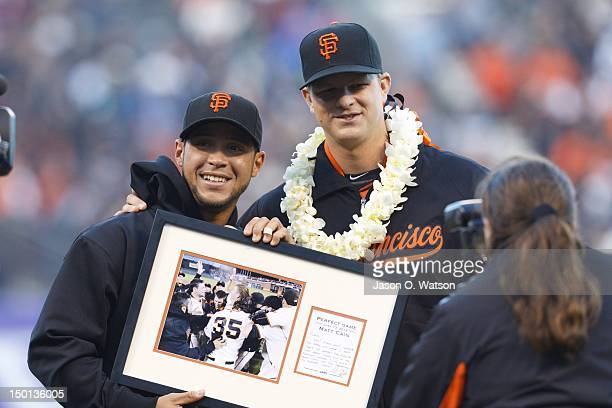 Matt Cain of the San Francisco Giants presents a framed photograph to teammate Gregor Blanco for a catch made during Cain's perfect game on June 13...