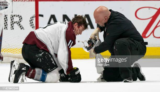 Matt Calvert of the Colorado Avalanche is attended to by a team trainer after getting hit with a shot during NHL action against the Vancouver Canucks...