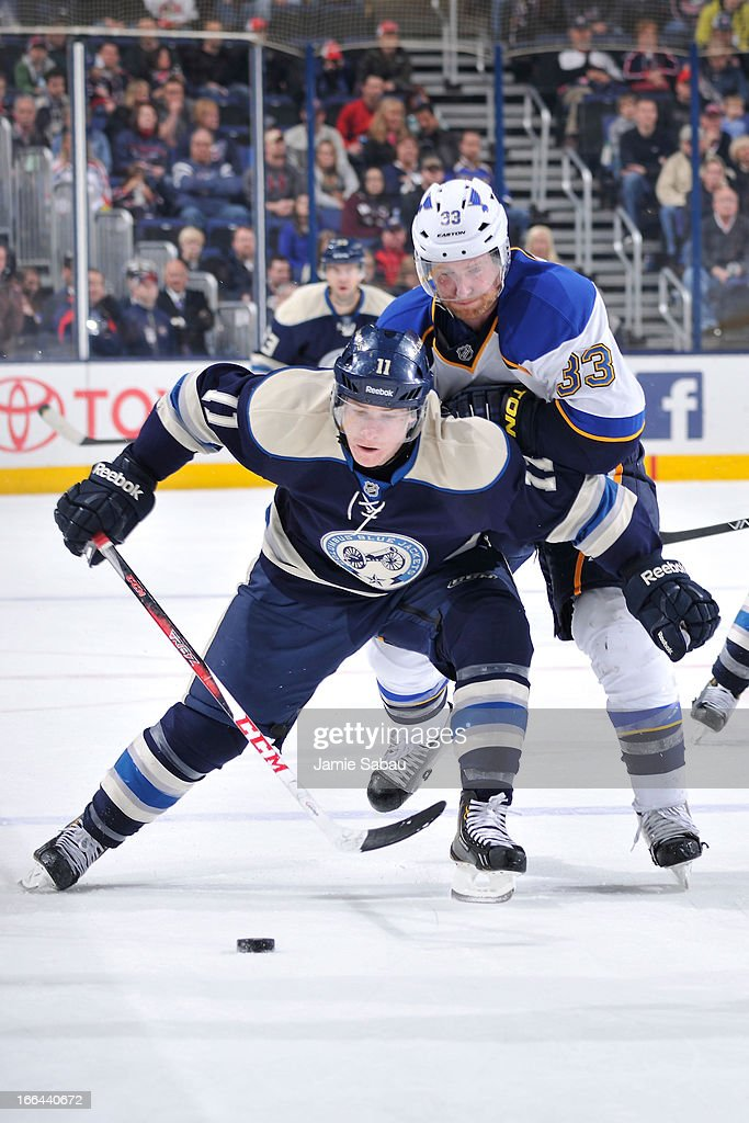 Matt Calvert #11 of the Columbus Blue Jackets and Jordan Leopold #33 of the St. Louis Blues battle for the puck during the third period on April 12, 2013 at Nationwide Arena in Columbus, Ohio. Columbus defeated St. Louis 4-1.