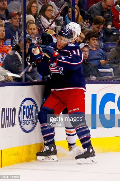 Matt Calvert of the Columbus Blue Jackets checks Kris Russell of the Edmonton Oilers while chasing after the puck during the game on December 12 2017...